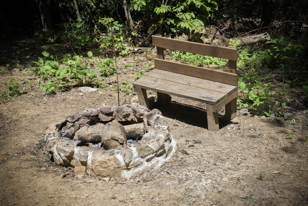 rustic bench with rock fire pit